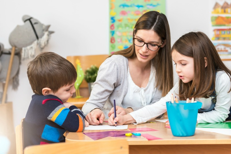SMALL Brunette teacher with glasses and kids at table
